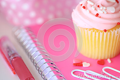 A pink cupcake with sprinkles, a pink notebook, paperclips and a pen.