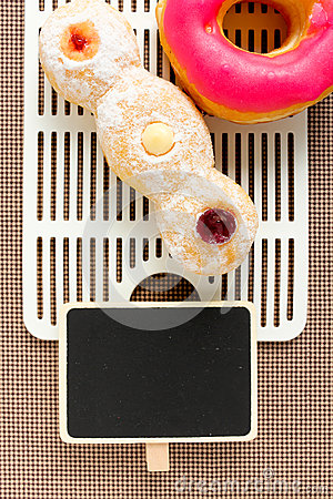 Pink donut and trio on tablecloth with blackboard