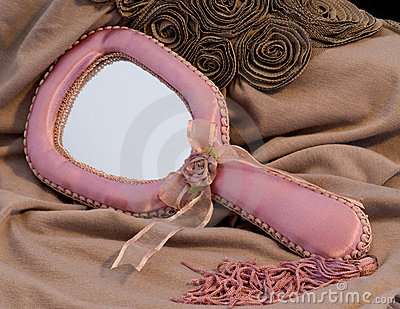Pink fabric hand mirror on knit blouse
