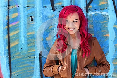 Pink hair girl against a blue wall
