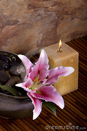 Pink lily flower and candle on bamboo