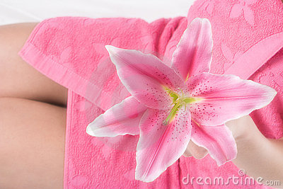 Pink lily in woman hand on pink towel