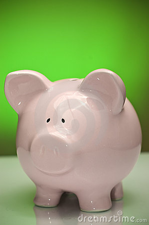 Pink piggy bank on green background