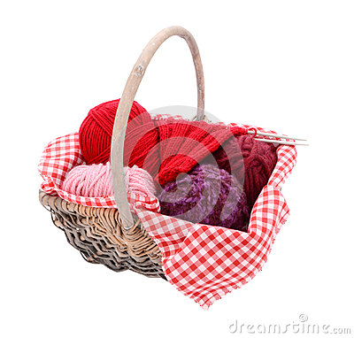 Pink, purple and red yarn with knitting in a basket
