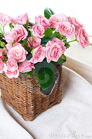 Pink roses in a wicker basket and linen fabric