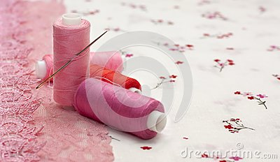 Pink spool of thread on a floral fabric