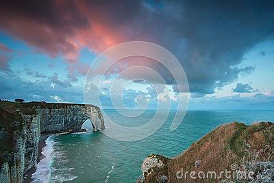 Pink stormy sunrise over cliffs in ocean