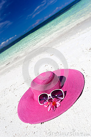 Pink summer hat on beach with sunglasses and plumeria