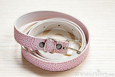 Pink women style belt on a light wooden background