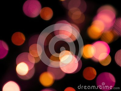 Pink and yellow abstract round blurred lights in a black background Stock Photo