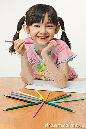 Pintura agradable de la niña con los lápices