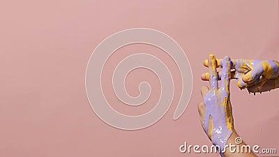 Pintura que vierte en las manos masculinas cruzadas en una muestra del hashtag en un fondo coloreado, publicidad creativa, concep almacen de metraje de vídeo