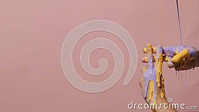 Pintura que vierte en las manos masculinas cruzadas en una muestra del hashtag en un fondo coloreado, publicidad creativa, concep almacen de video