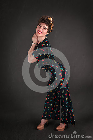 Pinup Girl in Flowered Outfit Stands Against Grey Background