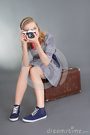 Pinup woman with camera sitting on brown retro suitcase