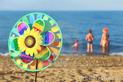 Pinwheel toy on beach, family standing in water