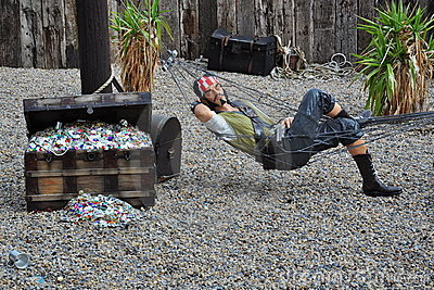 Pirata en hamaca por el pecho de tesoro Foto editorial