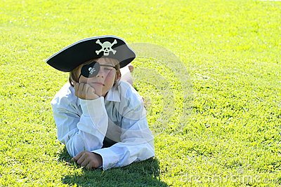 Pirate boy lying on grass