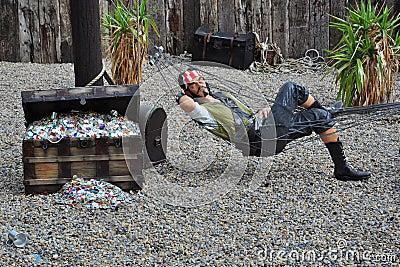 Pirate dans l hamac par le coffre de trésor Photo éditorial