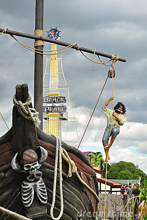Pirate with knife in mouth climbing ship mast Editorial Photo