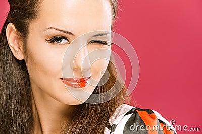 Piscadelas dark-haired bonitas da menina