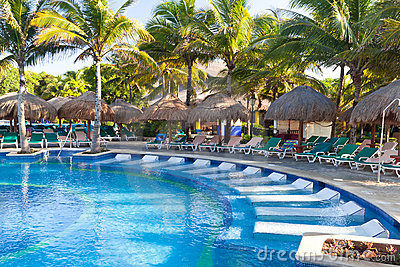 Piscina tropical con los sunbeds