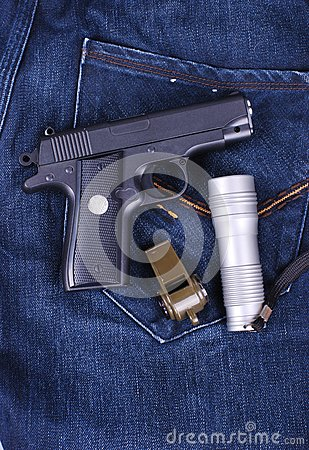 Pistol,flashlight and whistle on cloth of jean