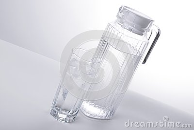 Pitcher and glass with ice cubes of mineral water