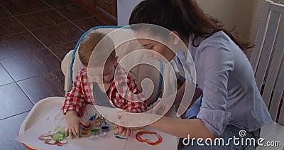Pittura del piccolo bambino con le mani e le capacità motorie fini di sviluppo e di creatività video d archivio