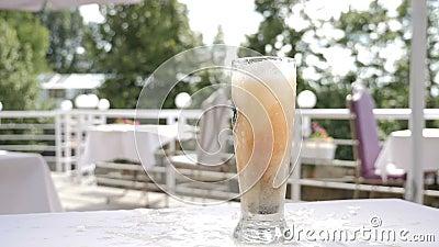 Piwny che?botanie Piwna napój porcja Mali flass z ciemnym alkoholicznym cieczem spada w szkło z piwem swobodny ruch zdjęcie wideo