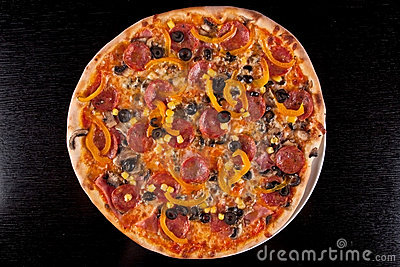 Pizza on black wood table. Clipping path included.