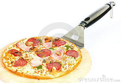 Pizza with ham, mushrooms, salami and pesto sauce