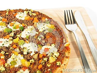 Pizza mit Tischbesteck-Nahaufnahme