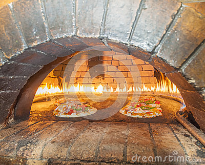 Pizzas cooking in an open oven