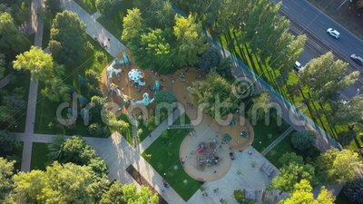 Plac zabaw dla dzieci w parku w mieście w słoneczny wieczór, widok z powietrza zdjęcie wideo
