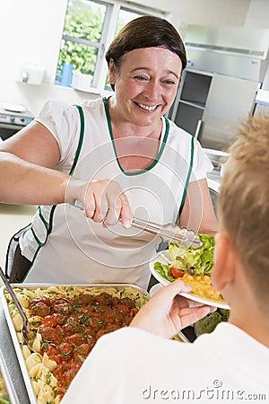 Placa de la porción de Lunchlady del almuerzo en una escuela