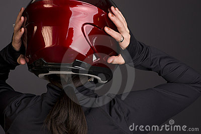 Woman Places Helmet on her Head Rear View