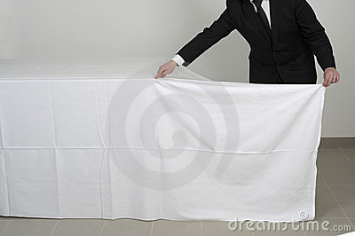 Placing a tablecloth on a buffet table