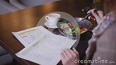 Plan dietético, joven hermosa y oportuna chica supervisa su dieta y cuenta con contenido calórico sentado en la mesa en el café,  almacen de video