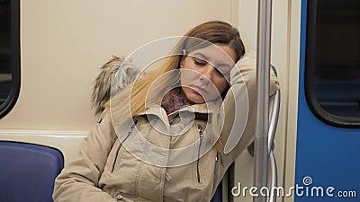Plan rapproché de femme caucasienne de sommeil d'A dans une veste chaude dans le souterrain de train banque de vidéos