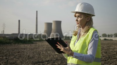 Plan rapproché de la femme réussie d'ingénieur de travailleur à l'aide du comprimé numérique inspectant la centrale de pétrole et banque de vidéos