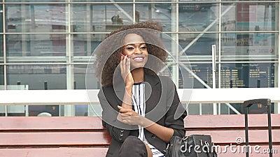 Plan rapproché de la jeune femme de sourire attirante d'affaires d'afro-américain s'asseyant sur le banc à l'aéroport et parlant  banque de vidéos