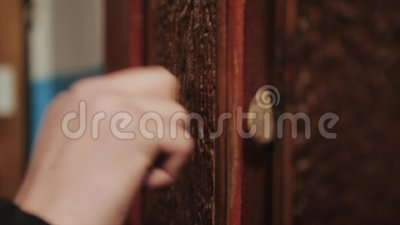 Plan rapproché de main frappant sur la porte