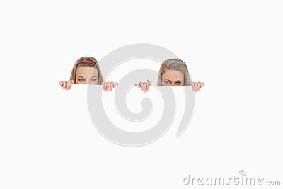 Plan rapproché de jeunes femmes se cachant derrière un signe blanc