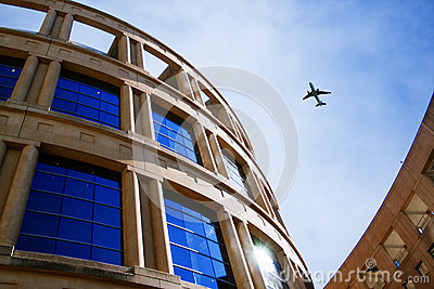Plane flying over curvy building