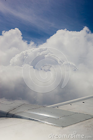 Plane wing, ground, clouds and sky