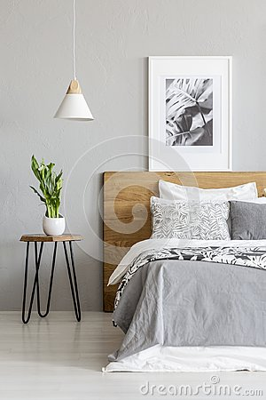 Free Plant On Table Next To Wooden Bed In Grey Bedroom Interior With Stock Image - 121951611