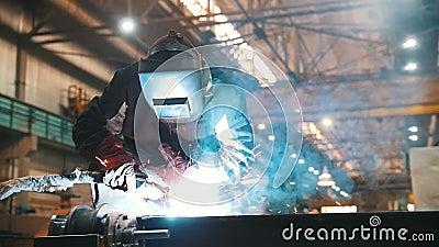 Planta da constru??o Um homem em um capacete usando uma m?quina de solda para conectar detalhes vídeos de arquivo