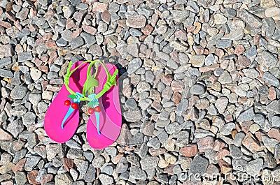 Plastic bright flip-flops on the pebble