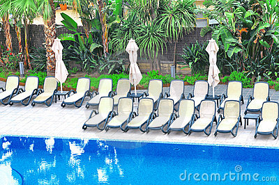 plastic chairs and umbrellas near swimming pool